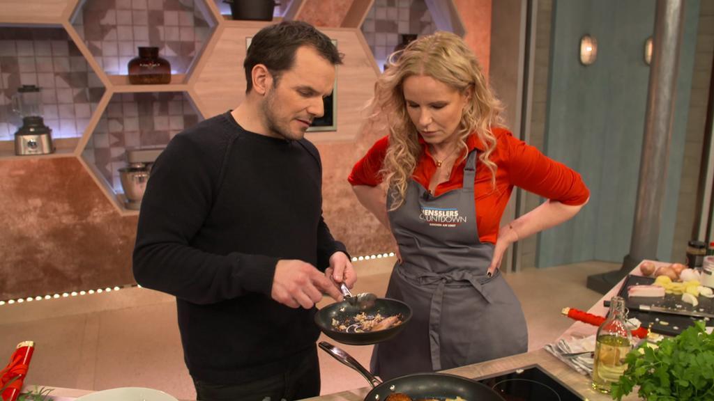 Steffen Henssler zeigt Moderatorin Katja Burkard, wie er Bratkartoffeln und Chili con Carne zubereitet.