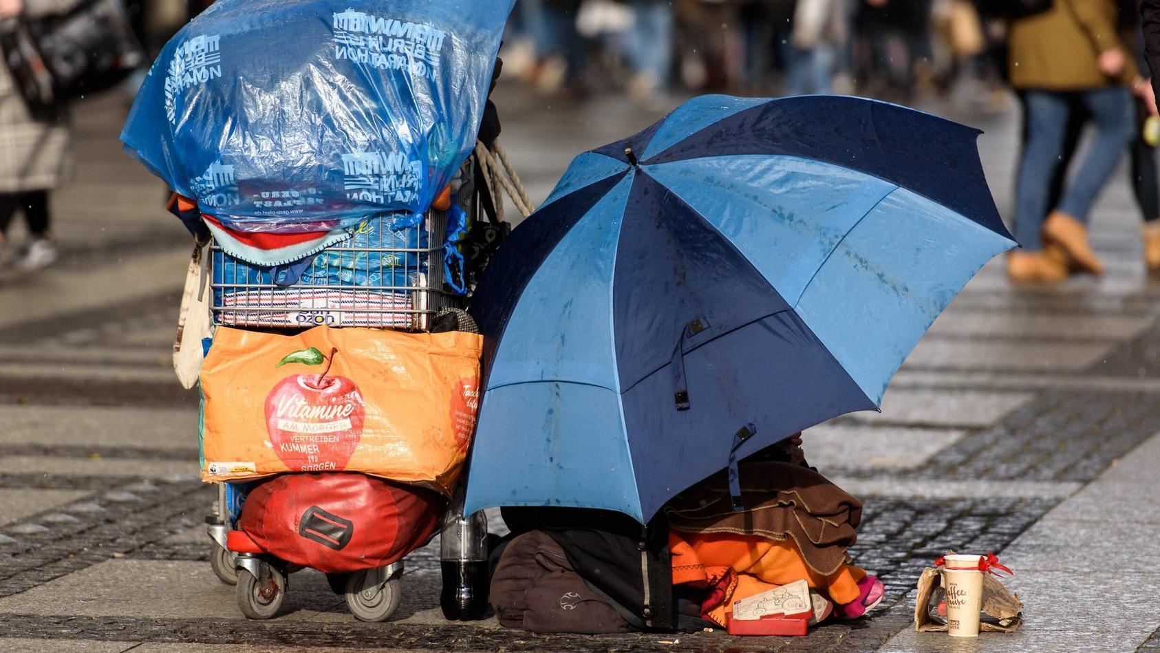 Feature Bild Obdachlosigkeit Deutschland, Berlin - 09/03/2019: Im Bild ist ein Obdachloser Mensch mit Schirm und Einkauf.