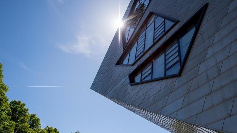 Die Sonne ist hinter einem Teil vom Libeskind-Bau der Leuphana Universität zu sehen. Foto: picture alliance / Philipp Schulze/dpa/Archivbild