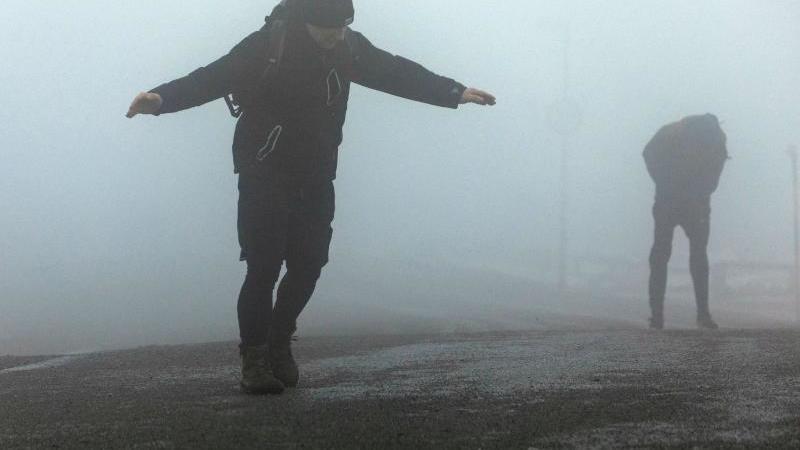 Touristen kämpfen gegen die Windböen auf dem Brocken. Foto: Bernd März/dpa/Archivbild