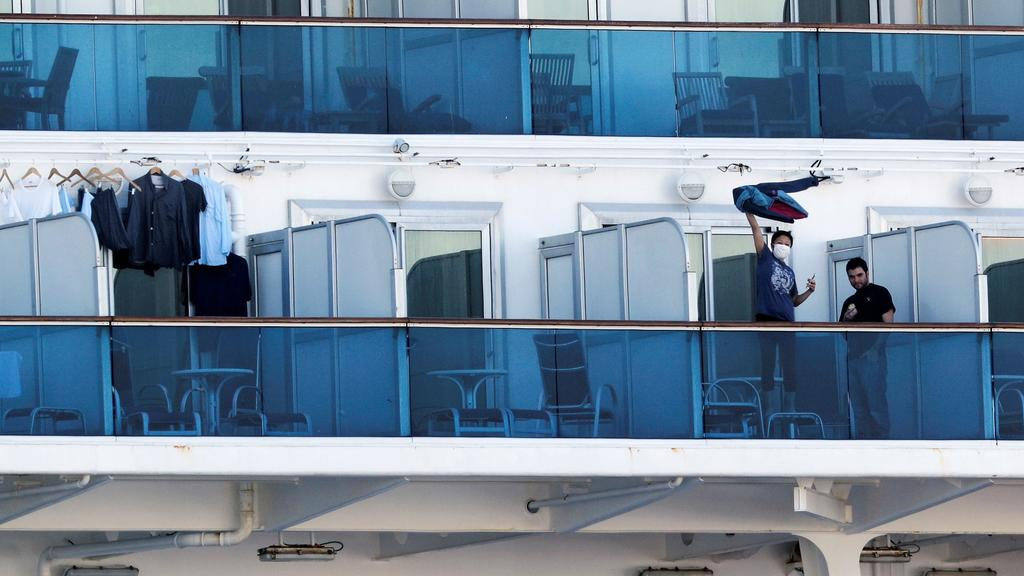A passenger waves a jacket towards a woman (not pictured) on land as they communicate via phone at the balcony of a cabin on the cruise ship Diamond Princess, as the vessel's passengers continue to be tested for coronavirus, at Daikoku Pier Cruise Te