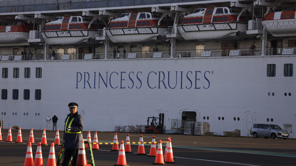 A security guard stands near the quarantined Diamond Princess cruise ship Thursday, Feb. 13, 2020, in Yokohama, near Tokyo. Life on board the luxury cruise ship, which has dozens of cases of a new virus, can include fear, excitement and soul-crushing