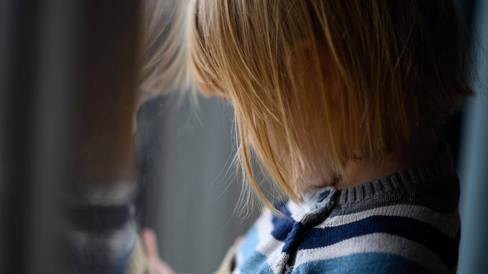 Kind schaut aus dem Fenster/Symbolbild