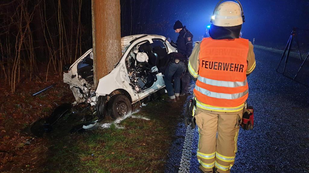 Unfall in Brandenburg: Zwei Polizisten und ein Feuerwehrmann stehen neben dem stark beschädigten Auto.