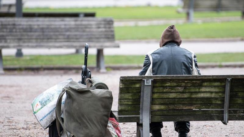 Ein Mann sitzt mit seinen Habseligkeiten auf einer Parkbank. Foto: Sebastian Gollnow/dpa