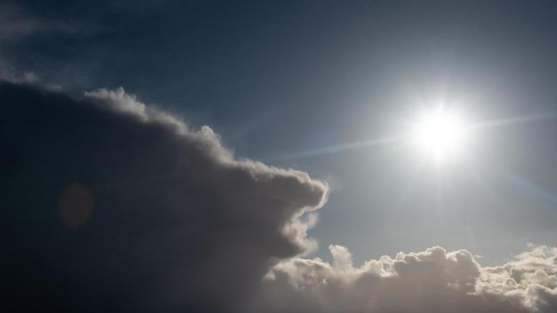 Die Sonne scheint neben dunklen Regenwolken. Foto: Swen Pförtner/dpa