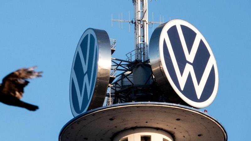 Zwei Vögel fliegen vor dem Logo der Volkswagen AG auf dem VW-Tower. Foto: David Hutzler/dpa/Archivbild