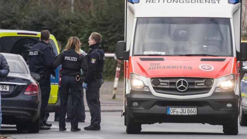 Ein Rettungswagen, Polizisten und deren Fahrzeuge stehen in der Maingaustraße. Foto: Frank Rumpenhorst/dpa