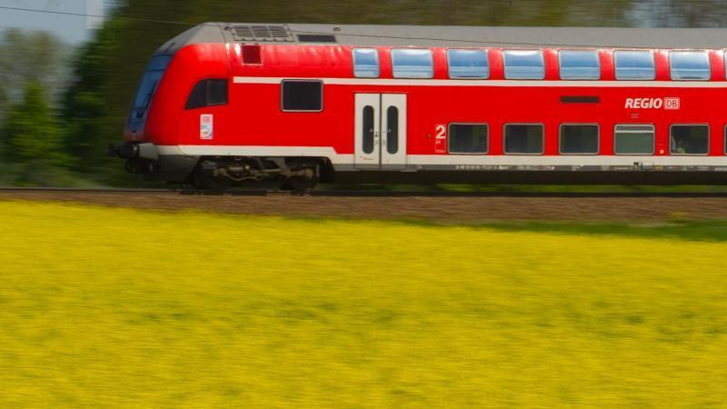 Ein Regionalzug fährt an einem blühenden Rapsfeld vorbei. Foto: Patrick Pleul/zb/dpa/Archivbild