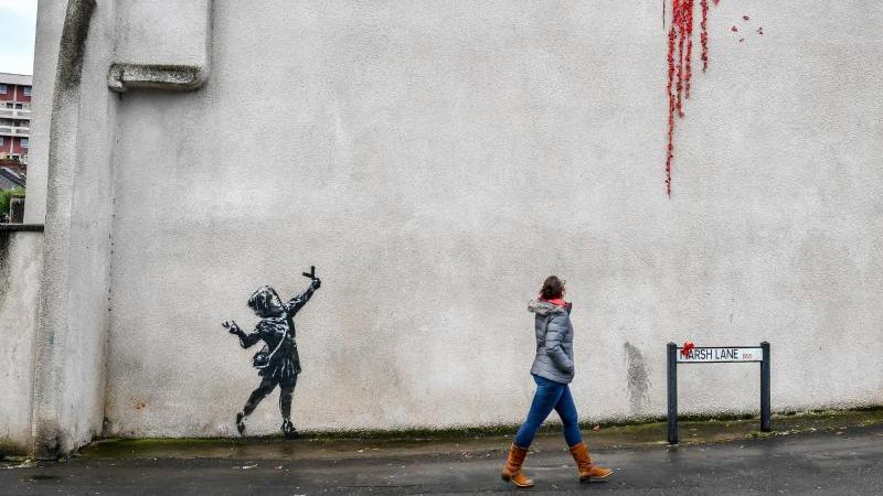 Eine Frau geht an einer Hauswand an einem Street-Art-Werk vorbei. Foto: Ben Birchall/PA Wire/dpa
