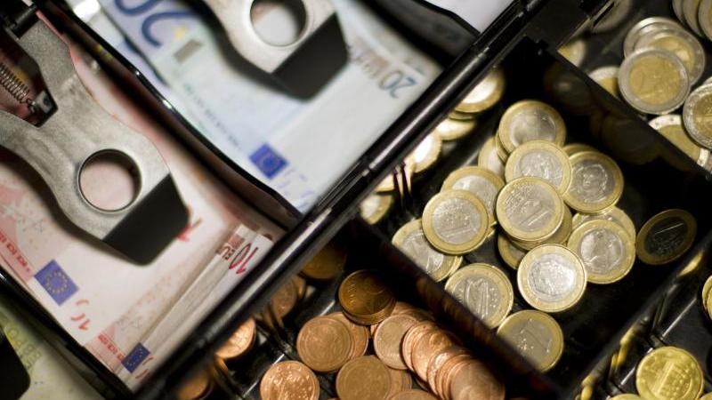 Bargeld in einer Kasse. Foto: Daniel Reinhardt/dpa/Archivbild