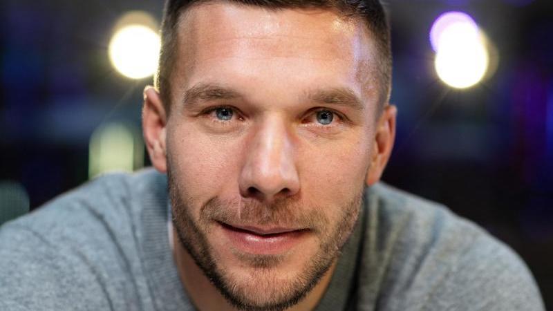 Lukas Podolski lächelt in die Kamera. Foto: Bernd Thissen/dpa/Archiv