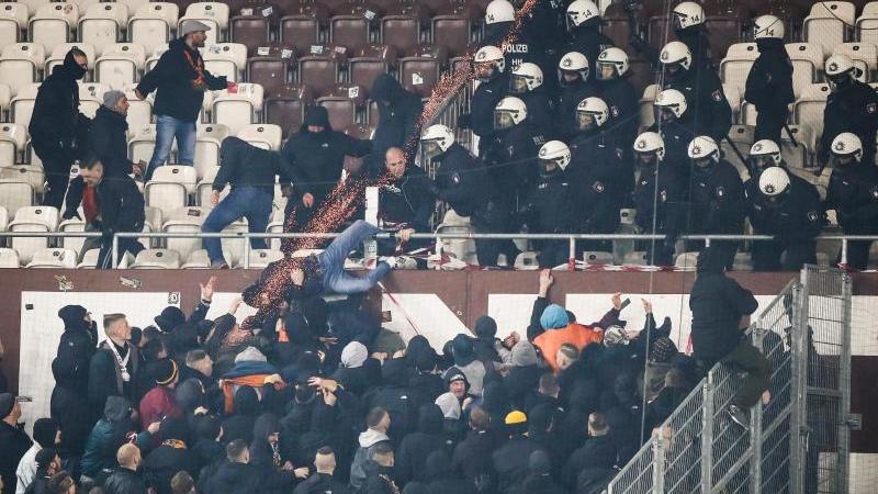 Polizeikräfte drängen randalierende Fans von Dynamo Dresden zurück in den Gästeblock. Foto: Christian Charisius/dpa