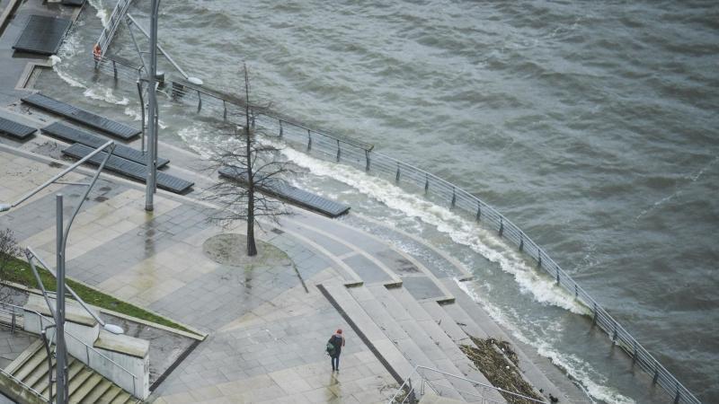 Fußgänger gehen bei Sturm und Regen durch die Hamburger Hafencity an einer Aussichtsterrasse entlang, die von der Elbe umspült wird. Foto: Axel Heimken/dpa/Archivbild
