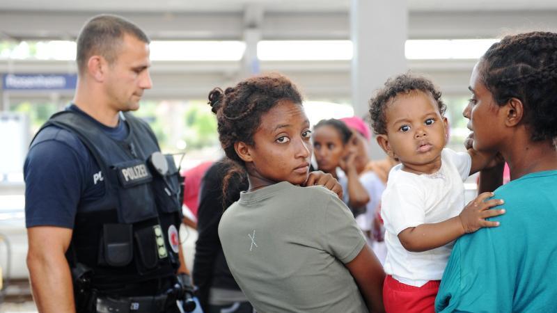 Ein Polizist und zwei Frauen sowie ihr Kind warten auf den Beginn der interkulturellen Schulung. Foto: Andreas Gebert/dpa/Archivbild
