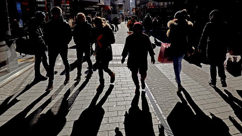 Passanten werfen in einer Kölner Fußgängerzone lange Schatten. Foto: Oliver Berg/dpa