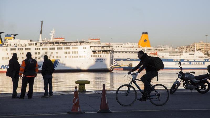 Passanten stehen vor den angedockten Fähren im Hafen von Piräus. Foto: Socrates Baltagiannis/dpa