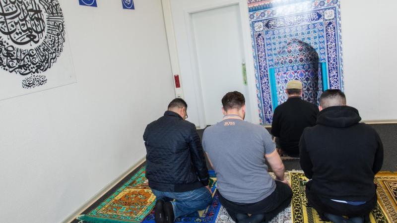 Ein muslimische Seelsorger (2.v.r.) betet während einer Gebetsstunde gemeinsam mit Häftlingen. Foto: Silas Stein/dpa