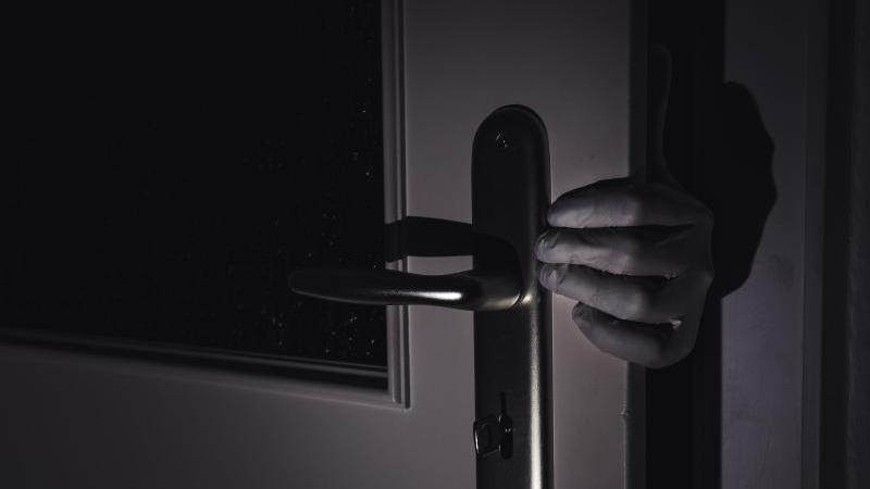 Eine Person bricht in eine Wohnung ein. Foto: Nicolas Armer/dpa