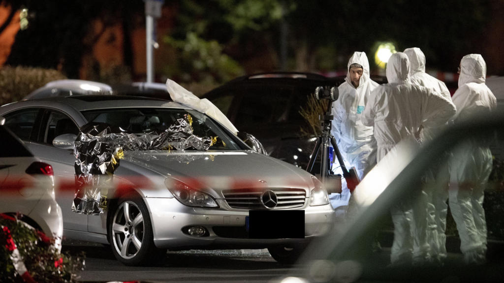Police forensic personnel investigate at the scene after a shooting in central Hanau, Germany Thursday, Feb. 20, 2020. A German man shot and killed several people at different locations in a Frankfurt suburb overnight. (AP Photo/Michael Probst)