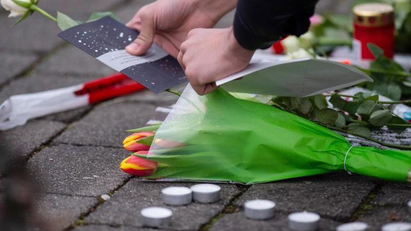 Eine Frau legt als Zeichen der Trauer eine Karte und Blumen an einem Tatort in Kesselstadt nieder. Foto: Dorothee Barth/dpa