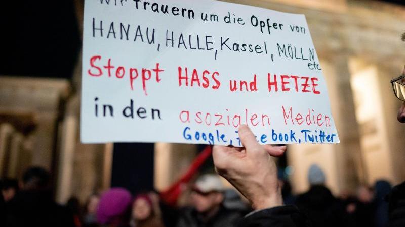 Teilnehmer gedenken der in Hanau getöteten Menschen bei einer Mahnwache am Brandenburger Tor. Foto: Kay Nietfeld/dpa