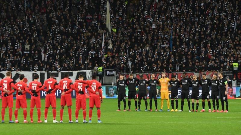 Die Spieler von Eintracht Frankfurt (r) und RB Salzburg stehen bei einer Schweigeminute zusammen. Foto: Arne Dedert/dpa