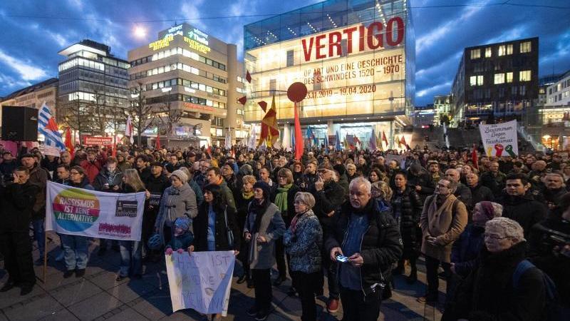 Menschen stehen während einer Gedenkveranstaltung für die Opfer von Hanau auf dem Schloßplatz. Foto: Sebastian Gollnow/dpa