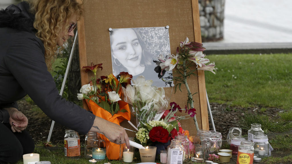 FILE - In this Dec. 12, 2018, file photo, a woman lights candles during a candlelight vigil for murdered British tourist Grace Millane at Cathedral Square in Christchurch, New Zealand. At a sentencing hearing at the Auckland High Court on Friday Feb.