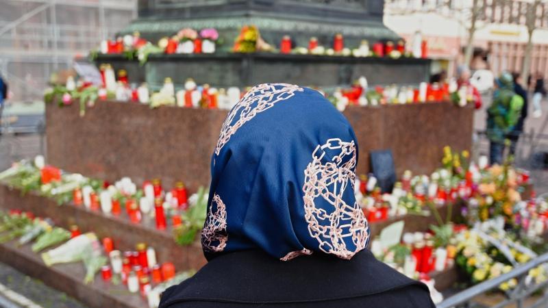 Eine Frau steht vor dem Hanauer Brüder Grimm Denkmal, an dem Blumen und Kerzen niedergelegt worden sind. Foto: Nicolas Armer/dpa