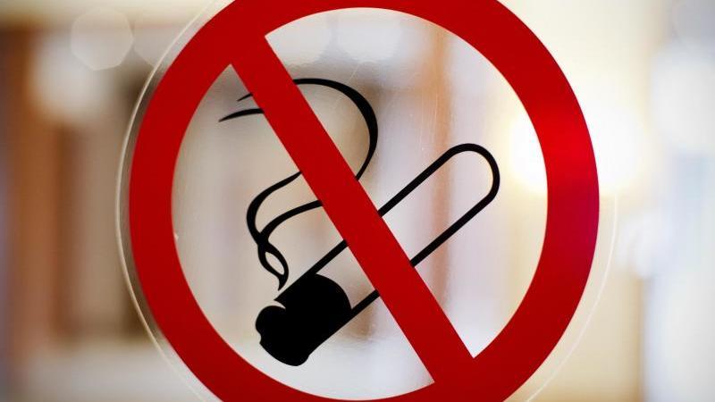 Ein Rauchverbotsschild hängt an einer Glasscheibe. Foto: picture alliance / dpa/Archivbild
