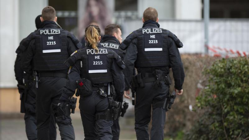 Polizisten gehen an einem Tatort in Kesselstadt. Foto: Dorothee Barth/dpa/Archiv