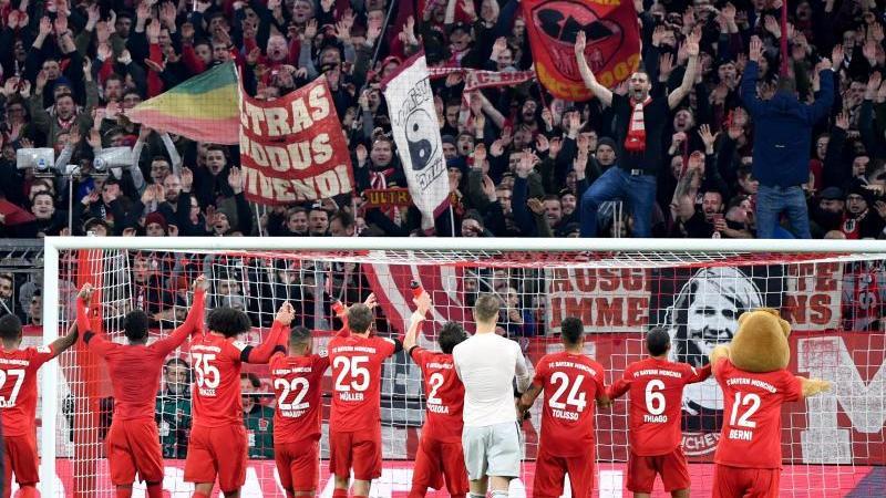 Jubel bei Fans und Spielern: Der FC Bayern hat mit 3:2 gewonnen. Foto: Peter Kneffel/dpa