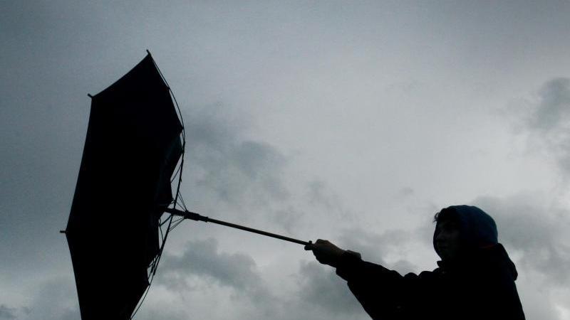 Eine Windböe erfasst den Regenschirm einen Spaziergängers. Foto: picture alliance / Karl-Josef Hildenbrand/dpa/Archivbild