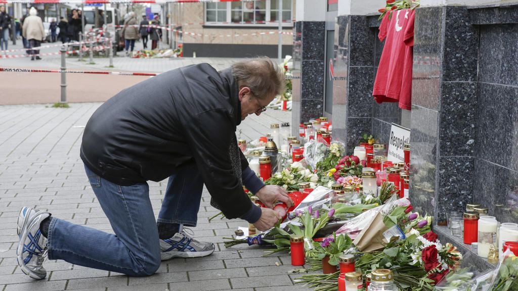 Germany: Anti-fascist protest in Hanau A mourner lays down a candle at one of the memorials for the Hanau shooting. Several thousand people marched through Hanau three days after the Hanau Shootings, to remember the victims and to protest against the