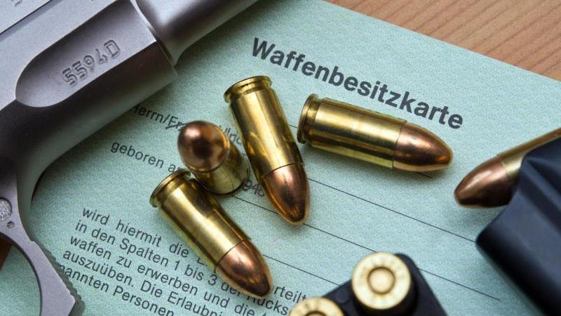 Eine Kaliber 9 mm Pistole, Patronen und ein Magazin liegen auf einer Waffenbesitzkarte. Foto: Patrick Pleul/zb/dpa/Archivbild