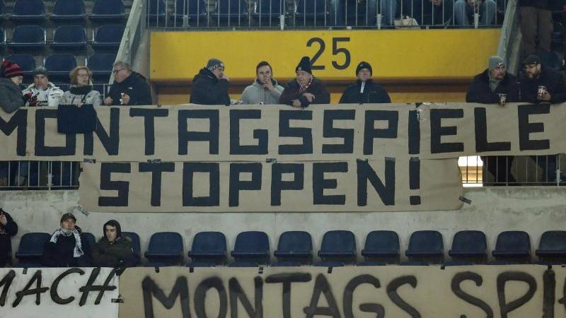 """Eintracht-Frankfurt-Fans haben ein Plakat mit der Aufschrift """"Montagsspiele stoppen!"""" aufgespannt. Foto: Uwe Anspach/dpa/Archivbild"""