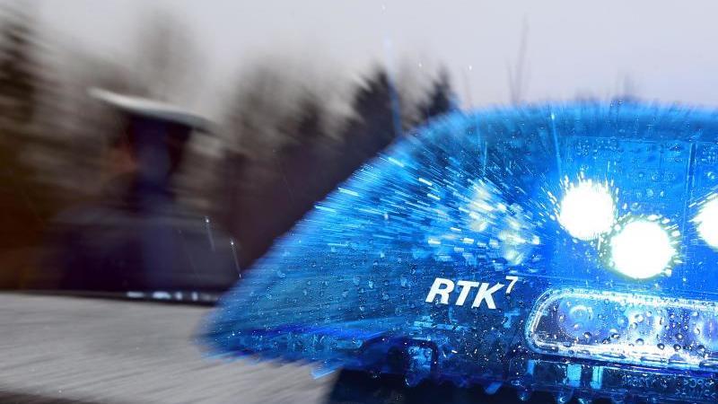 Ein Polizist steht vor einem Streifenwagen. Foto: Karl-Josef Hildenbrand/dpa/Archivbild