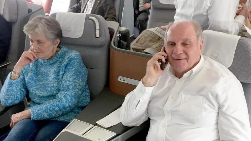 Uli Hoeneß (r), Ehrenpräsident des FC Bayern, telefoniert neben seiner Frau im Flugzeug nach London. Foto: Klaus Bergmann/dpa