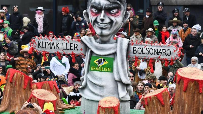 """Der Motivwagen """"Klimakiller Bolsonaro"""" zieht beim Rosenmontagszug durch die Menge. Foto: Federico Gambarini/dpa"""
