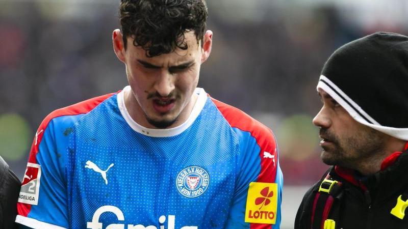 Kiels Janni Serra (l) reagiert nach seiner Verletzung enttäuscht. Foto: Frank Molter/dpa/Archivbild