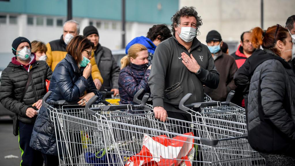 dpatopbilder - 23.02.2020, Italien, Casalpusterlengo: Menschen tragen Atemschutzmasken und stehen vor einem Supermarkt in einer Schlange. Nach dem Tod zweier Menschen sind Teile des öffentlichen Lebens zum Erliegen gekommen. Kein europäisches Land ha