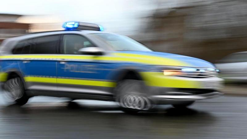 Ein Streifenwagen mit eingeschaltetem Blaulicht fährt über eine Straße. Foto: Carsten Rehder/dpa/Archivbild