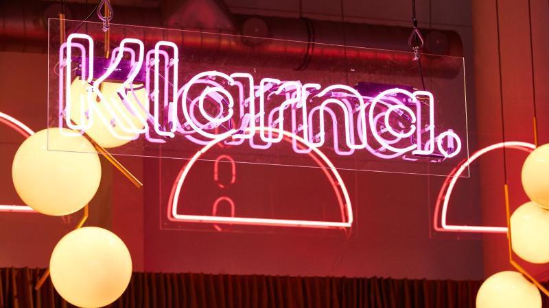 """Die Leuchtschrift """"Klarna"""" hängt am Stand der gleichnamigen Firma auf einer Marketing-Fachmesse. Foto: Georg Wendt/dpa/Archiv"""