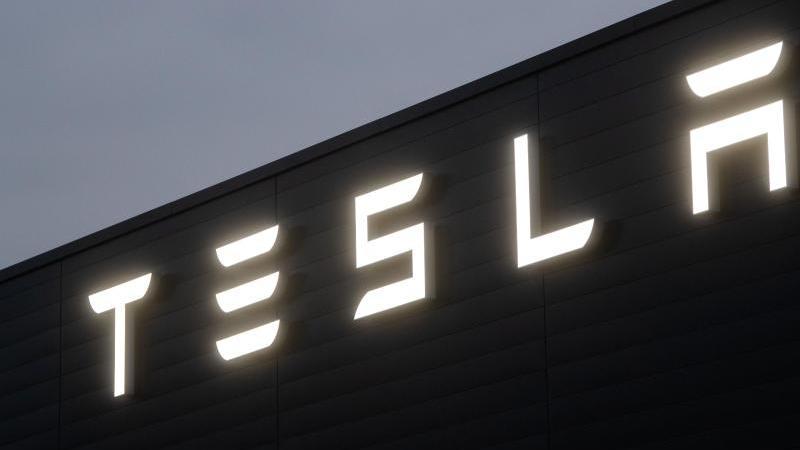Ein Schriftzug leuchtet auf einem Verkaufsgeschäft und Service Center des Herstellers Tesla. Foto: Julian Stratenschulte/dpa/Archiv