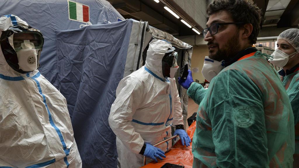 25.02.2020, Italien, Turin: Mitarbeiter inSchutzanzügen stehen in einem Krankenhaus neben einer Liege. Bei dem neuen Coronavirus steigt in Italien die Zahl der Toten und Infizierten weiter an. Foto: Diego Puletto/SOPA Images via ZUMA Wire/dpa +++ dp