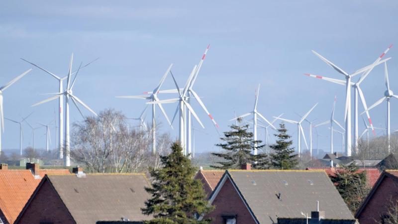 Windkraftanlagen stehen hinter einer Wohnsiedlung. Foto: Carsten Rehder/dpa/Archivbild