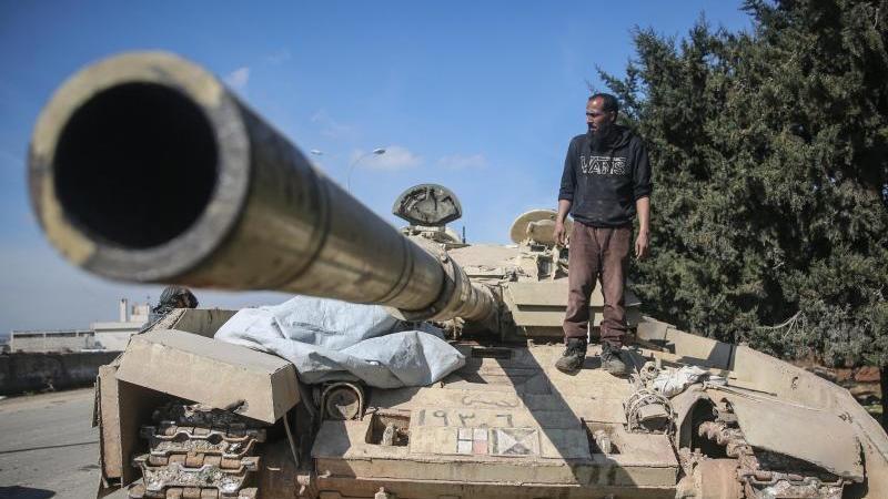 Ein Kämpfer der Nationalen Befreiungsfront (NFL) steht auf einem Panzer der syrischen Regierungstruppen. Foto: Anas Alkharboutli/dpa