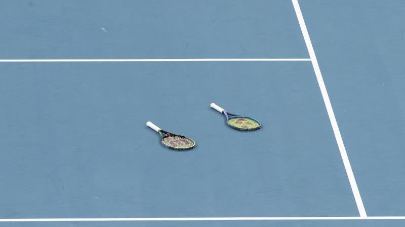 Zwei Tennischläger liegen auf dem Spielfeld. Foto: Craig Golding/AAP/dpa/Archivbild