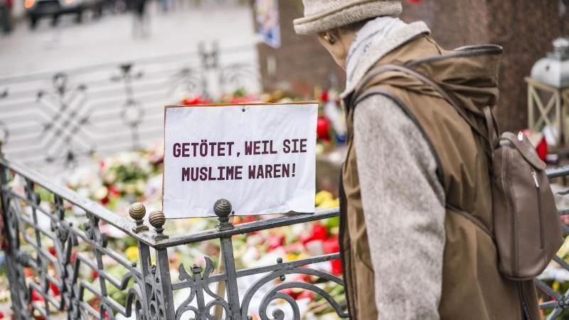 Eine Frau steht auf dem Marktplatz am Denkmal der Brüder Grimm, an dem die Bürger mit Blumen, Plakaten und Kerzen ihre Trauer zum Ausdruck bringen. Foto: Frank Rumpenhorst/dpa/Frank Rumpenhorst/dpa